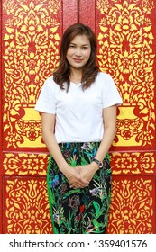 Asian woman in southern native Thai style pattern paint pants in with traditional Thailand Buddhist temple architecture.