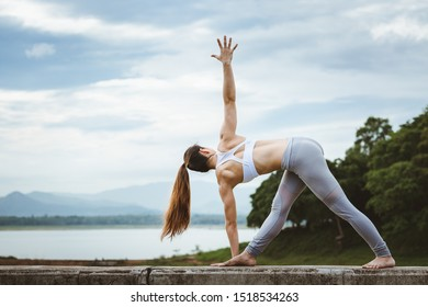 Asian woman with sport bra doing yoga fitness exercise for relax and healthy at lake in morning, Nature background, Concept outdoor sport and health