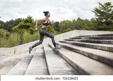 Asian woman sport woman running upstairs on city stairs