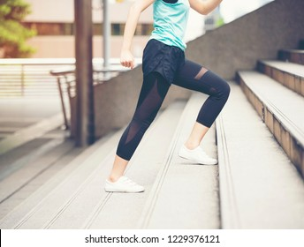 Asian woman in sport wear running upstairs in the city background.