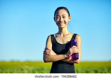 Asian woman in sportswear with water bottle standing in field. Runner girl with arms crossed holding sipper bottle. Half body portrait of sportswoman resting, smiling and looking at camera
