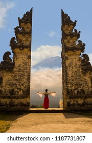 Asian woman spreading arms in front of Bali volcano Mount Agung through the beautiful and majestic gate of the hindu Pura Lempuyan temple of Indonesia in Asia holidays travel destination