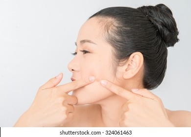 Asian woman squeezing pimples