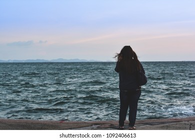 Asian woman stand alone to wait for someone near beautiful sea and colorful sky with vintage tone.