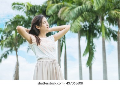 Asian woman stand in the garden with freshness emotion in the morning with blue sky and cloud
