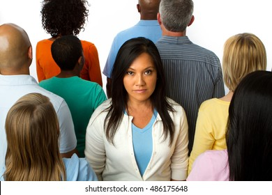 Asian woman standing alone in a crowd.