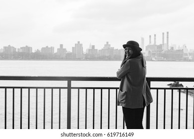 Asian Woman Standing in Brooklyn Looking at Manhattan on Rainy Day