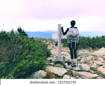 An asian woman standing by a wooden marker and hiking on Tuckerman Ravine trail with mountain range background in summer on Mt. Washington in the White Mountains of New Hampshire United States.