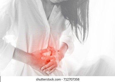 Asian woman standing hand touching her stomach pain during period, chocolate cyst concept