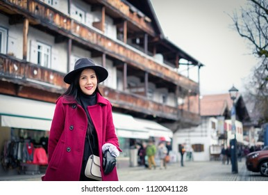 Asian woman standing on main street in Oberammergau with beautiful view of old town city and building paintings in background, Oberammergau, Germany
