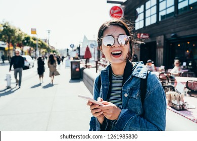 Asian woman standing on old port street using cellphone waiting for friends in front the restaurant outdoors cheerfully smiling. young girl searching direction to hotel in busy urban san francisco.