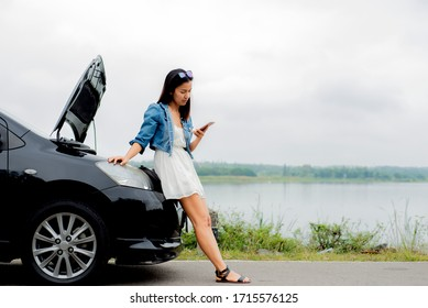 Asian woman standing  on roadside with car breadown using mobile phone , female using  smartphone with damaged car after a car accident , Insurance assistance Concept