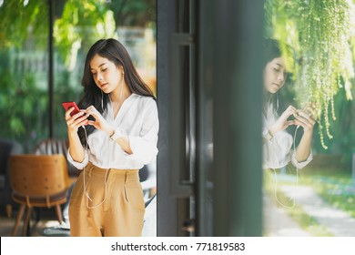 asian woman standing and using smart phone