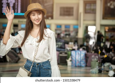 An Asian woman is standing, waving, greeting or saying goodbye when arriving at the train station, traveling concept.
