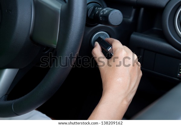 asian woman starting the car.