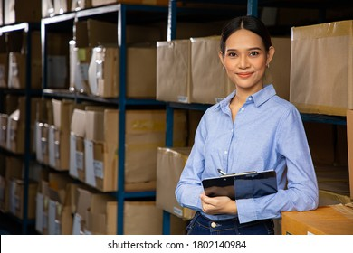 Asian woman storehouse manager smiling with his occupation.Thai warehouse staff holding document file for check quanlity products.Local logistic distribution.