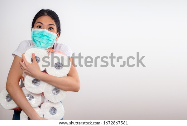 An Asian woman storing tissue toilet paper during Coronavirus outbreak or Covid-19, Concept of Covid-19 quarantine. Wuhan epidemic outbreak. Dangerous COVID virus, Doomsday panic people panic lockdown