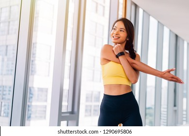 Asian woman stretching arms at the gym. Fitness female model looking out the window indoors with copy space