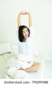 Asian woman stretching in bed after wake up in the morning