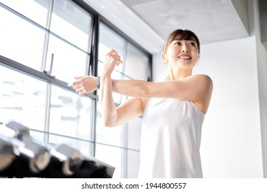 Asian woman stretching in a training gym