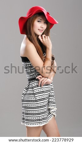 Asian Woman In Striped Tube Top And Flare Skirt Set With Red Hat
