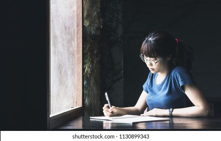 Asian woman student use pen write message on book after education out time.