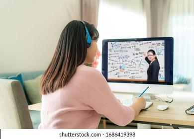 家庭のリビングルームで、教師とコンピューターを使ったアジアの女子学生ビデオ会議e – ラーニング。Eラーニング、オンライン、教育、インターネットのソーシャル・ディスタンシングは、COVID-19ウイルスから保護されます。