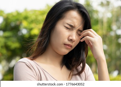 asian woman suffering from irritated eye; concept of optical health care, red eye allergy, eye care, allergic or itching or dry eye inflammation; young adult asian woman model