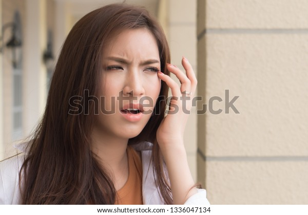 asian woman suffering from irritated eye; concept of optical health care, eye care, allergic or itching or dry eye; 20s young adult asian woman model
