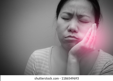 Asian woman suffering from toothache and have to see dentist. Concept of teeth problem.