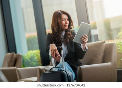Asian woman with suitcase sitting in airport waiting area. Businesswoman sitting at airport lounge with tablet.