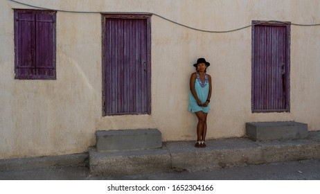 Asian Woman in sunglasses and hat standing in front of traditional Greek house with purple shutters and doors in village of Eressos on islands of Lesvos