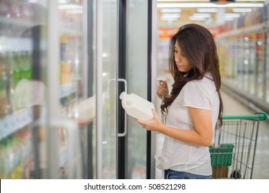 Asian woman in a supermarket standing in front of the freezer and choose buying fresh milk bottle. concept drink milk for healthy