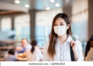 Asian woman with surgical mask face protection walking in crowds at restaurant or shopping mall