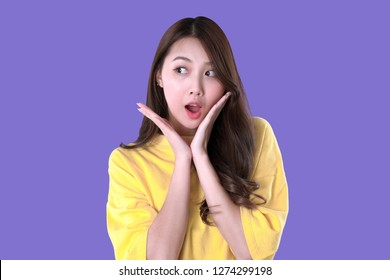 Asian woman surprise for special promotion and good product, yellow t-shirt clothing, purple background