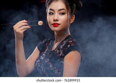 Asian woman with sushi eating sushi and rolls on a black background. Black Friday sushi sale.