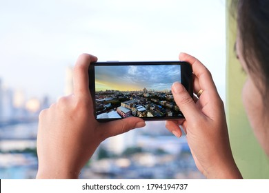 Asian woman take pictures of the buildings in the city. Sunrise time He uses a high-angle recording photo phone.Travel concepts and technology