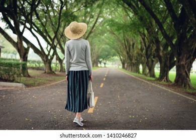 Asian woman take a walk on the way under the trees