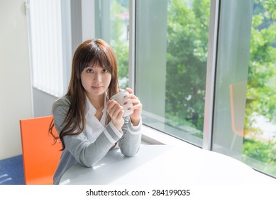 Asian woman takes a break with cup of coffee