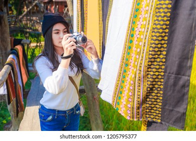 Asian woman taking photo colorful Thai sarongs fluttering in the wind, on the rice field meadow, Thailand