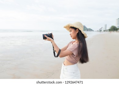 Asian woman taking photo on the tropical beach