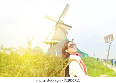 Asian woman taking photo with smartphone in Zaanse Schans, Netherlands