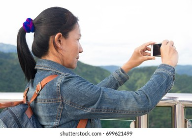 Asian woman taking photo with view mountain landscape
