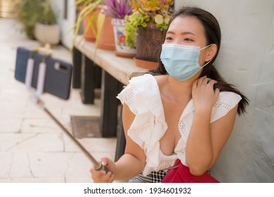 Asian woman taking selfie in Andalusia Spain in covid19 times - young happy and beautiful Korean girl in face mask taking selfie during holidays in Seville and Granada