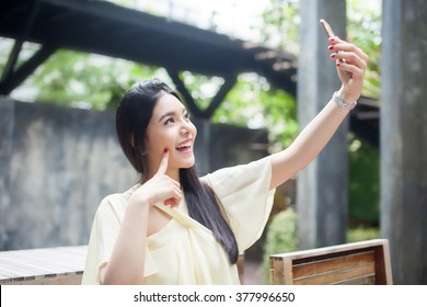 Asian woman taking a selfie with her phone in public park