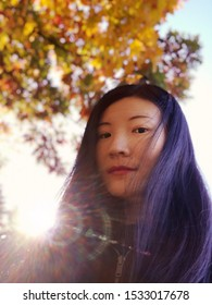 An asian woman taking a selfie photo with sunlight and autumn views background inside Burr pond state park in New England Connecticut United States on a sunny day.