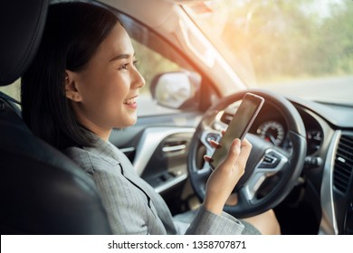 Asian woman talk by mobile calling texting and looking on a cellular phone while sitting in her car, driving under the influence, the driver is safely talking by smartphone in a car concept