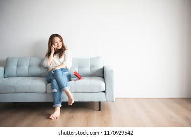 Asian woman talking in the living room sofa