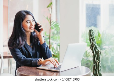 Asian woman talking on phone and working on laptop in a cafe
