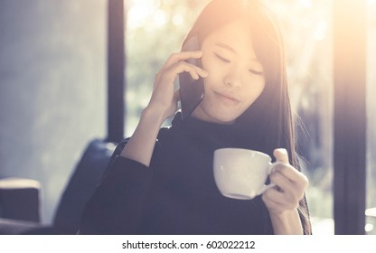 asian woman talking on the phone and holding cup of coffee